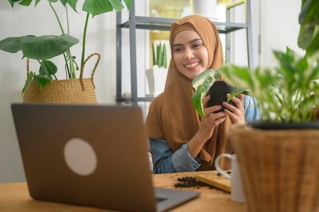 Een jonge moslimondernemer die met een laptop werkt, presenteert kamerplanten tijdens een online livestream thuis