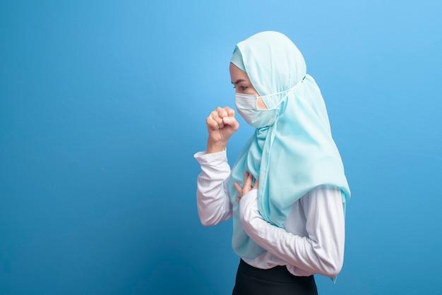 Een jonge moslimvrouw met hijab die een chirurgisch masker draagt dat zich ziek voelt en hoest over blauwe achtergrondstudio.