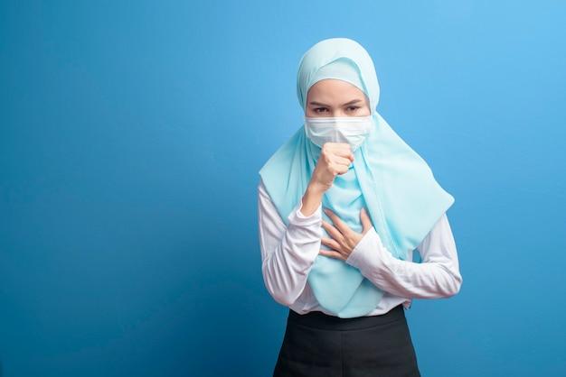 Een jonge moslimvrouw met hijab die een chirurgisch masker draagt, voelt zich ziek en hoest over blauw