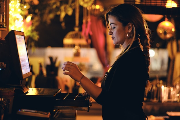 Een jonge ober bij haar eigen kleine restaurant 's nachts
