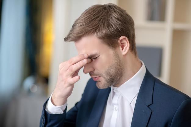 Een jonge officieel geklede man met hoofdpijn