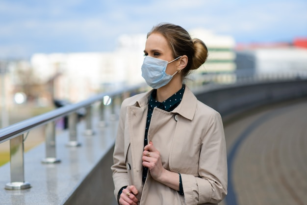 Een jonge onderneemster die een gezondheidsmasker draagt en op de telefoon in de stad spreekt