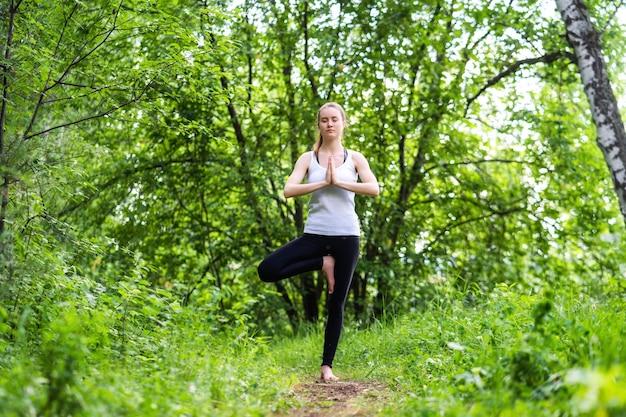 Een jonge ontspannen vrouw met gesloten ogen staat op een bos, haar armen zijn over haar borst gevouwen en in een yoga-boomhouding