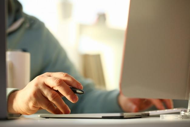 Een jonge ontwerper houdt pen van tablet in hand werkend aan nieuw project voor klant op gebied van bouwprojecten.