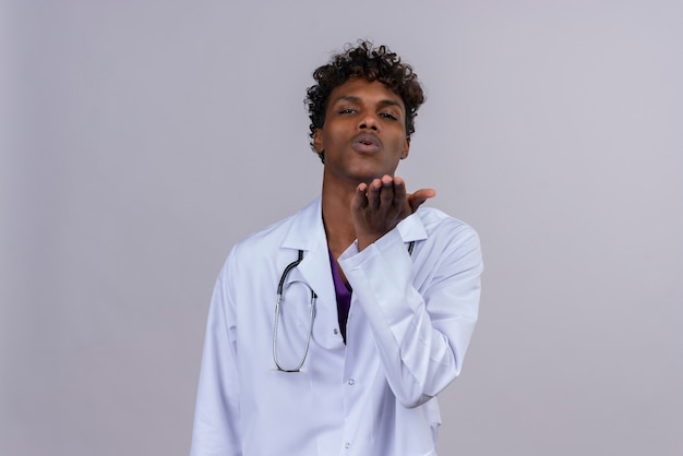 Een jonge opgewonden knappe donkere mannelijke arts met krullend haar die een witte jas draagt met een stethoscoop die een gebaar maakt van het sturen van een kus met zijn hand