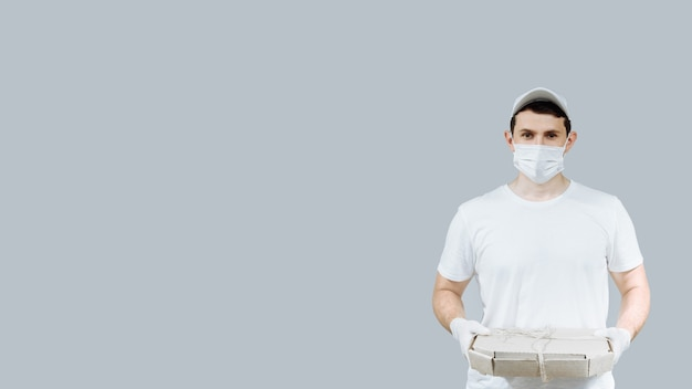 Een jonge pizzakoerier met een beschermend masker en handschoenen deelt dozen met voedsel uit en bezorgt een coronavirus tijdens een epidemie