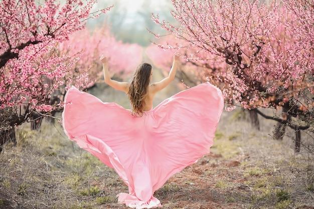 Een jonge prinses loopt in een bloeiende tuin. meisje in een luxe roze jurk met een trein. modieuze toning.