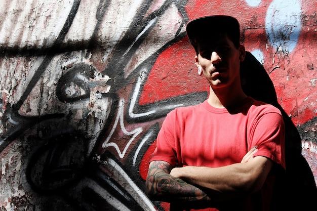 Een jonge rapper die tegen een muur leunt.