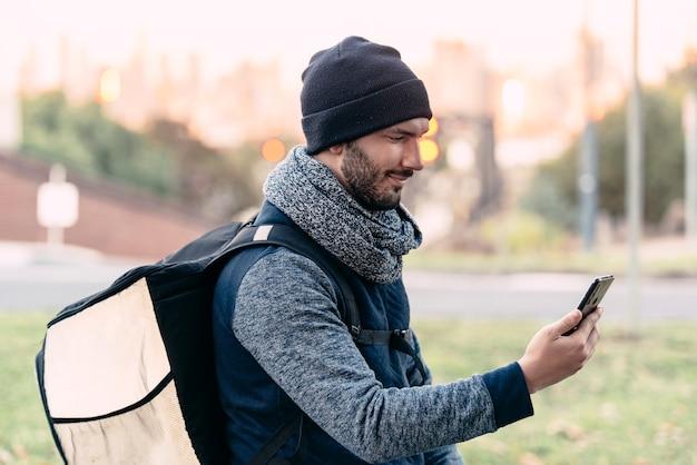 Een jonge rijder controleert zijn smartphone op nieuwe bezorgmaaltijden