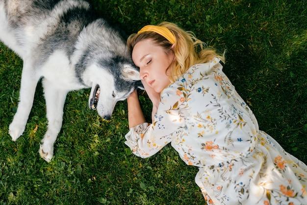 Een jonge romantische vrouw die met een hond op het gras ligt