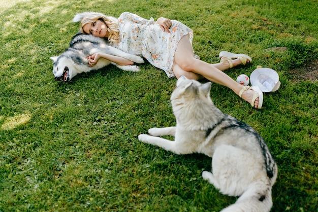 Een jonge romantische vrouw die met honden op het gras ligt