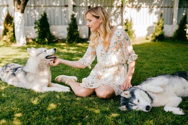 Een jonge romantische vrouw poseren met twee honden op het gras