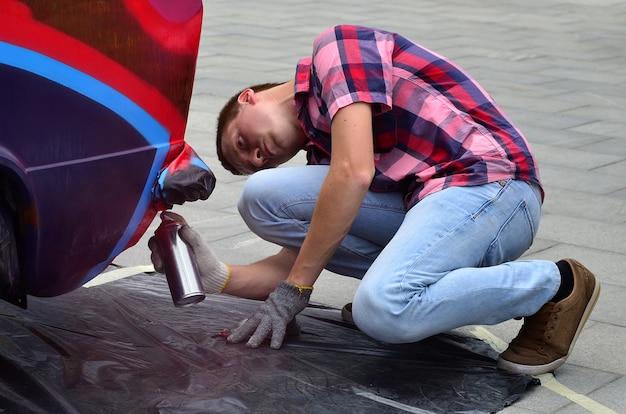 Een jonge roodharige graffitikunstenaar schildert een nieuwe kleurrijke graffiti