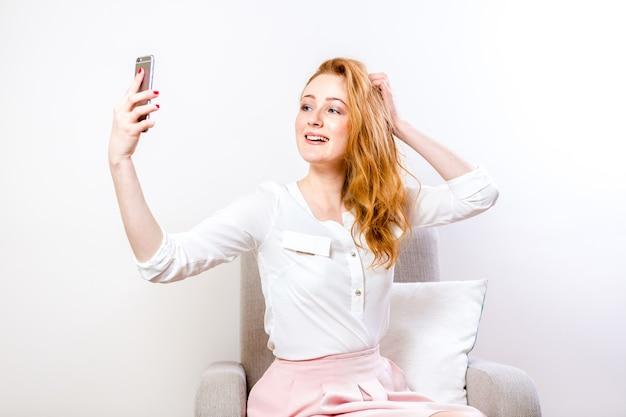 Een jonge roodharige vrouw gebruikt een mobiele telefoon voor videocommunicatie. student over online bekentenis op een witte achtergrond. vrouw chatten op sociaal netwerk live in studio
