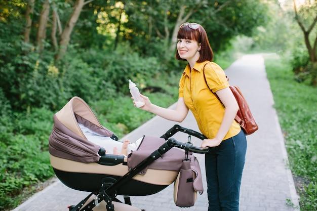 Een jonge roodharige vrouw in een geel shirt loopt met een kleine baby in een wandelwagen op een heldere zomerdag in het park