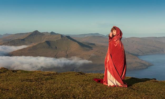 Een jonge roodharige vrouw in ouderwetse kleding met een felrode mantel blijft op het grasveld in de hooglanden. faeröer, denemarken