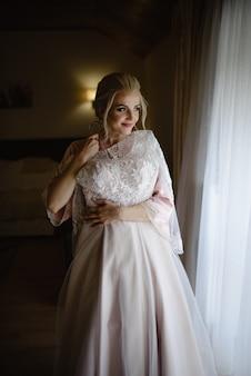 Een jonge schattige blonde bruid in een badjas probeert haar trouwjurk