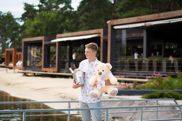 Een jonge schattige kerel wacht op een ontmoeting met zijn vriendin. wachten op de pier met champagne en een teddybeer. romantische date