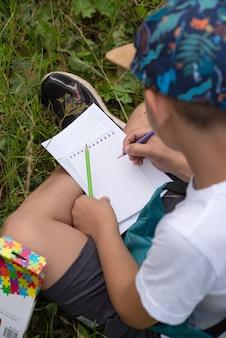 Een jonge schooljongen zit in een openluchtpark huiswerk te maken
