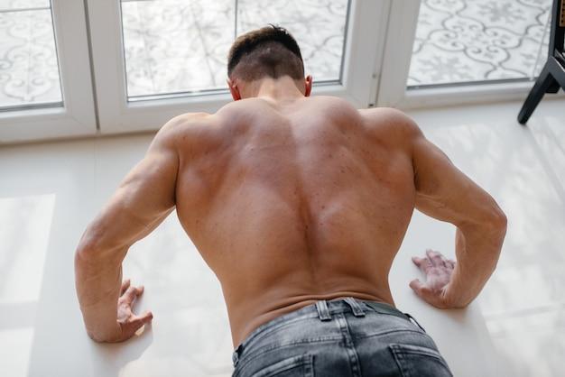 Een jonge sexy atleet met perfecte buikspieren doet push-ups in de studio topless in spijkerbroek. gezonde levensstijl, goede voeding, trainingsprogramma's en voeding voor gewichtsverlies.