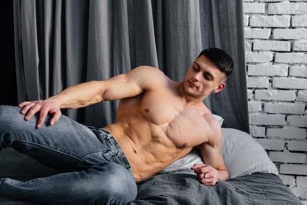 Een jonge sexy atleet met perfecte buikspieren ligt op het bed in de studio topless in spijkerbroek op de achtergrond. gezonde levensstijl, goede voeding, trainingsprogramma's en voeding voor gewichtsverlies.