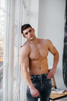 Een jonge sexy atleet met perfecte buikspieren poseert bij het raam in de studio topless in spijkerbroek op de achtergrond. gezonde levensstijl, goede voeding, trainingsprogramma's en voeding voor gewichtsverlies.