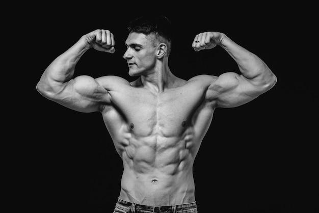 Een jonge sexy atleet met perfecte buikspieren poseert in de studio topless in spijkerbroek. gezonde levensstijl, trainingsprogramma's en voeding voor gewichtsverlies. zwart en wit.