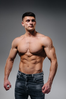 Een jonge sexy atleet met perfecte buikspieren poseert in de studio topless in spijkerbroek op de achtergrond. gezonde levensstijl, goede voeding, trainingsprogramma's en voeding voor gewichtsverlies.