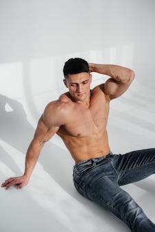 Een jonge sexy atleet met perfecte buikspieren zit op de grond in de studio topless in spijkerbroek op de achtergrond. gezonde levensstijl, goede voeding, trainingsprogramma's en voeding voor gewichtsverlies.