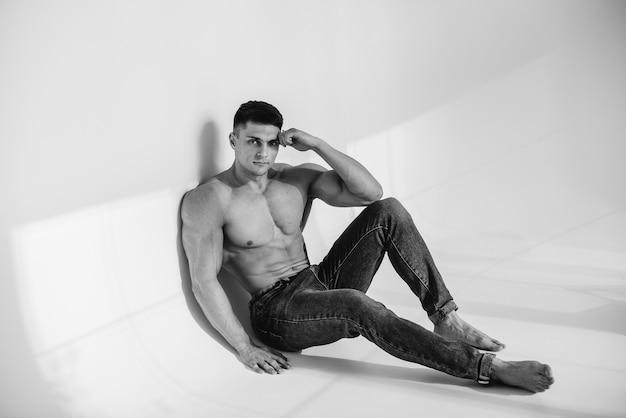 Een jonge sexy atleet met perfecte buikspieren zit topless in spijkerbroek in de studio. gezonde levensstijl, goede voeding, trainingsprogramma's en voeding voor gewichtsverlies. zwart en wit.