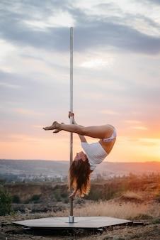 Een jonge sexy vrouw voert geweldige oefeningen uit op een paal tijdens een prachtige zonsondergang. dans. seksualiteit.
