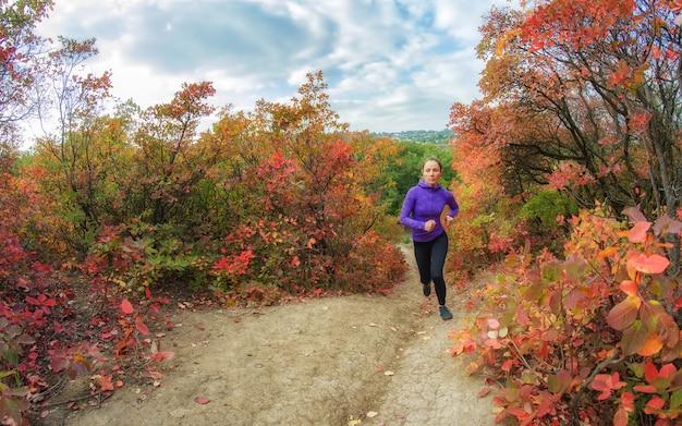 Een jonge slanke atletische vrouw in een zwarte legging en een blauw jasje rent in een kleurrijke rode herfstbosheuvel.
