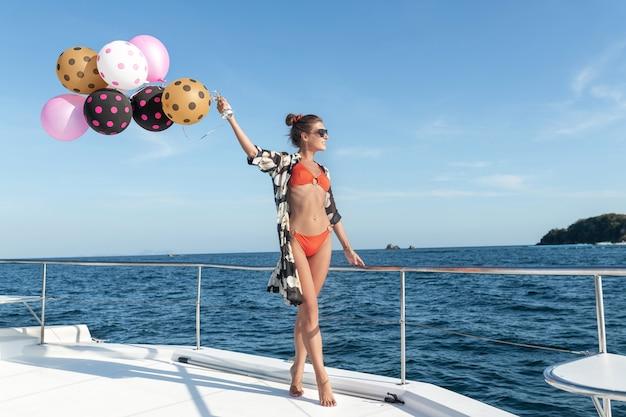 Een jonge slanke vrouw in een bikini staat op een luxe jacht met een heleboel helium ballonnen. feest en feest, zeereis. kopieer ruimte