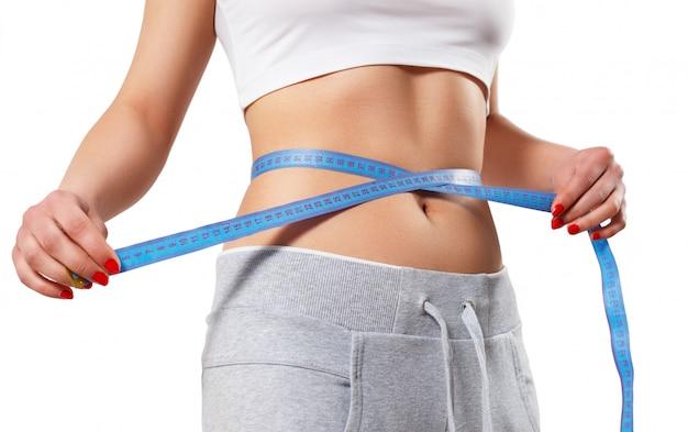 Een jonge slanke vrouw meet haar taille met een centimeterband.
