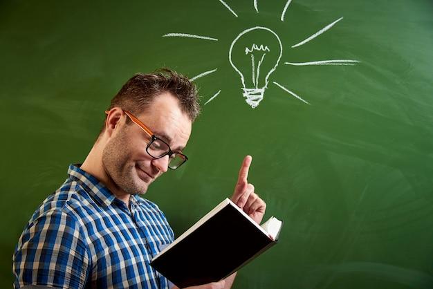 Een jonge slonzige man met bril is een boek aan het lezen, een idee komt voor de geest
