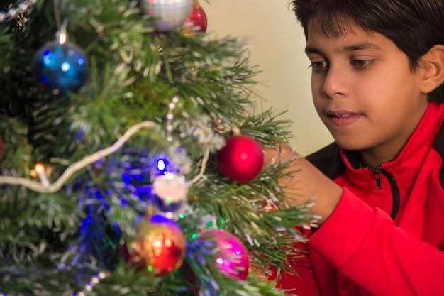 Een jonge soort die de kerstboom versiert