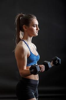 Een jonge sport dame met paardenstaart kapsel in fitness kleding training met dumbells