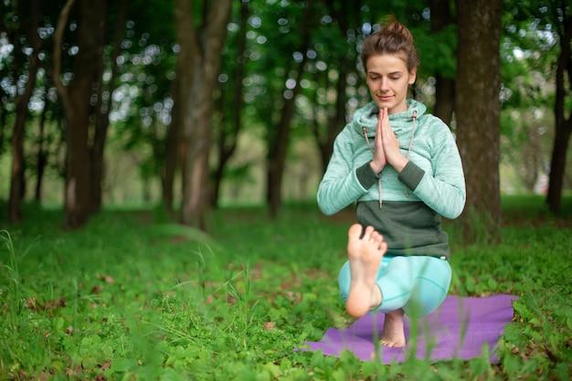 Een jonge sportvrouw beoefent yoga in een opgehouden groen zomerbos
