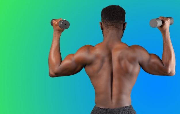 Een jonge sterke afro-amerikaanse man die vanaf de achterkant zijn halter optilt