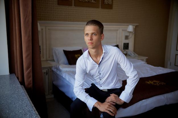 Een jonge stijlvolle en zakenman gaat naar een zakelijke bijeenkomst in een hotelkamer.