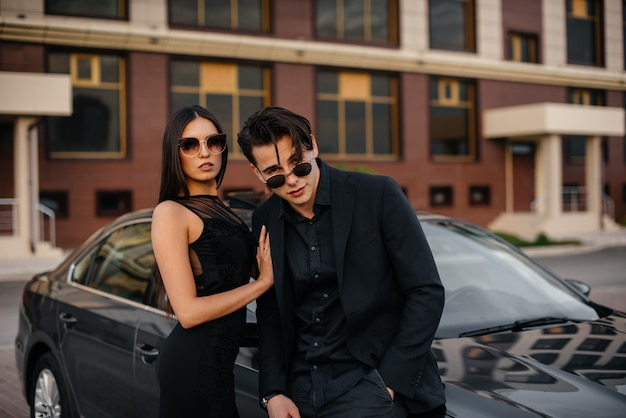 Een jonge stijlvolle paar in het zwart staat in de buurt van de auto bij zonsondergang. mode en stijl