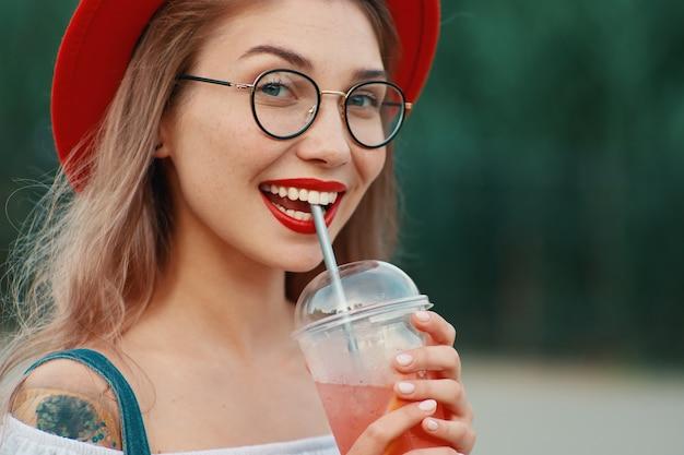 Een jonge stijlvolle vrouw met een drankje tijdens het kijken naar de camera