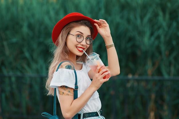 Een jonge stijlvolle vrouw met een verfrissend drankje tijdens het lopen