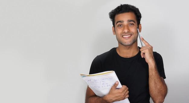 Een jonge student met boeken en pen geïsoleerde muur - onderwijsconcept