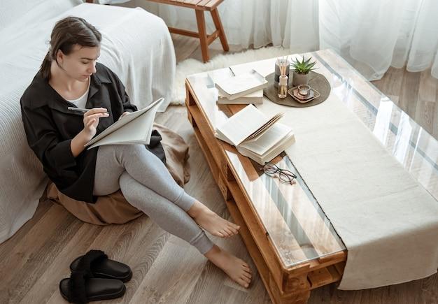 Een jonge studente doet thuis opdrachten, zittend met een notitieboekje in haar handen.