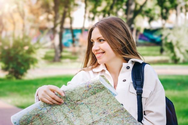 Een jonge studente loopt door de stad met een kaart en op zoek naar een manier. uitwisselingsstudenten concept
