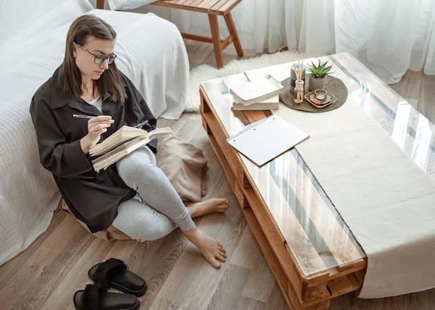 Een jonge studente met een bril doet thuis opdrachten, zittend op een poef met een notitieboekje in haar handen.