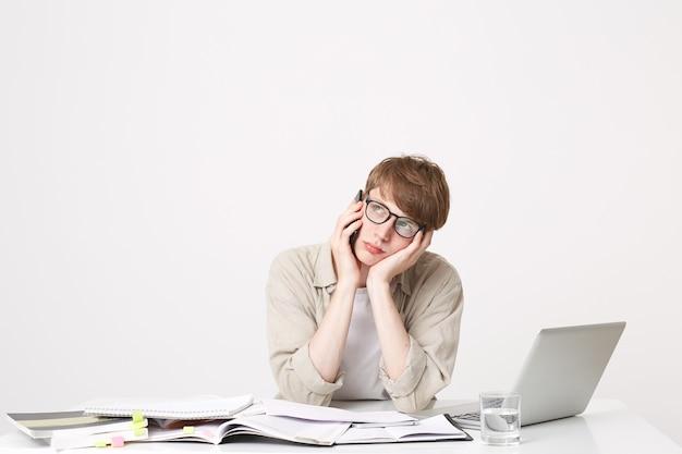 Een jonge studentenjongen zit aan de tafel en luistert naar iemand aan de telefoon