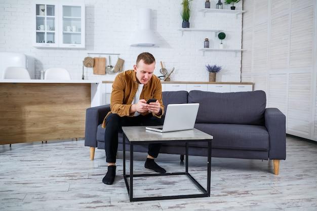 Een jonge succesvolle man zit thuis op de bank met een laptop en werkt. werken op afstand tijdens quarantaine.