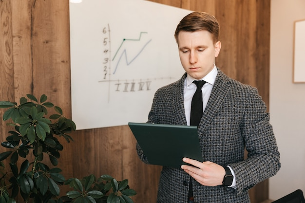 Een jonge succesvolle zakenman en kantoormedewerker met een lichte huid houdt een map met documenten in zijn handen, staat in zijn kantoor. een man werkt in een kantoor, maakt aantekeningen op papier.